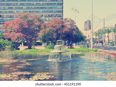Rabin Square of Tel Aviv.Recreation area with fountain,blossom plants and trees in the center of old town.The building of the local municipality in the background. Israel. Toned colors vintage photo
