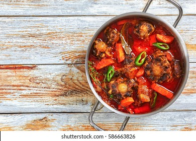 rabo de toro or beef tail stew with vegetables, thyme, red wine and jalapeno pepper chunks in cooking pot on old dark wooden table, authentic recipe, view from above, close-up