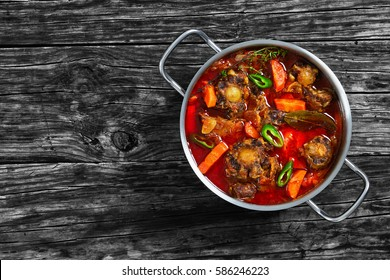 rabo de toro or oxtail stew  with vegetables, thyme, bay leaf, garlic and jalapeno pepper chunks in cooking pot on old dark wooden table, traditional spain cuisine, authentic recipe, view from above