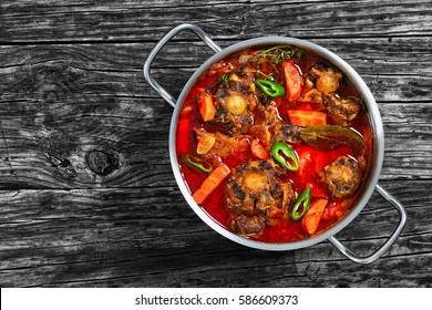 rabo de toro or oxtail stew with vegetables, herbs, red wine and jalapeno pepper chunks in cooking pot on old dark wooden table, traditional spain cuisine, authentic recipe, view from above, close-up