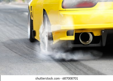 race car burns rubber off its tires in preparation for the race