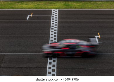 Race car racing on a track with motion blur.
