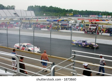 Race Cars returns to the pit after an accident during a NASCAR race.