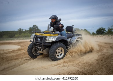 The race in difficult conditions on the sand on a quad bike.