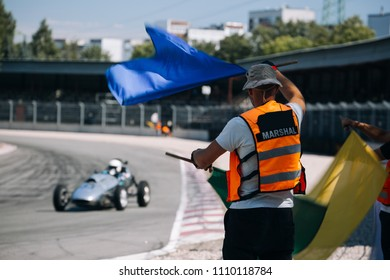 Race director show blue flag. Marshal of raceway inform classic formula junior driver with signal