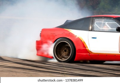 Race drift car with smoke Which professional driver drifting red car on race track as a sport car racer on street concept