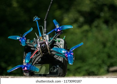 Race drone with blue propellers and transmitter with green background in nature and motors for drones and quadcopters for racing and fpv
