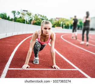 Race Fit and confident woman in starting position ready for running.Female athlete about to start a sprint looking away.young runner getting ready for a run on track.girl feet on race track on stadium