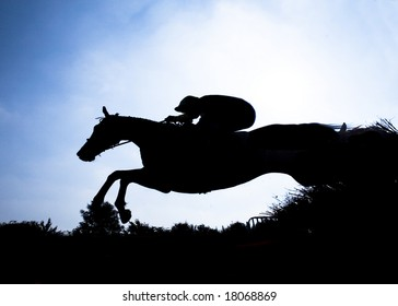 race horse jumping hurdle at speed photographed in silhouette