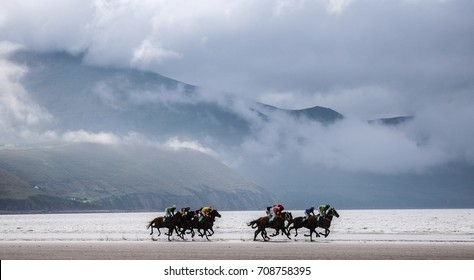 Race horses galloping on the beach with dramatic landscape background