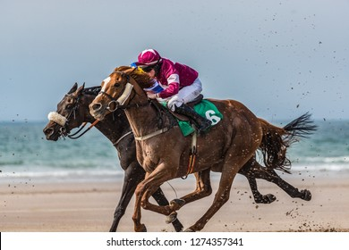 Race horses and jockeys competing on the beach