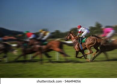 Race horses with jockeys runs the circuit.