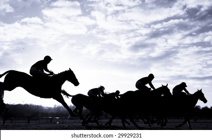 race horses jumping over a hurdle at speed photographed in silhouette with room for titles