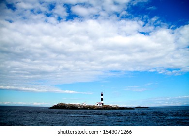 Race Rocks lighthouse and island in the Salish Sea set in a sunny day with white fluffy clouds.