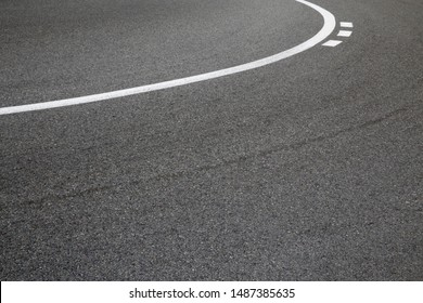 Race track. Speedway. Steep turn. Macro photo of road bend with solid and broken white marking. Curvilinear geometric background on the subject of car race or road traffic.