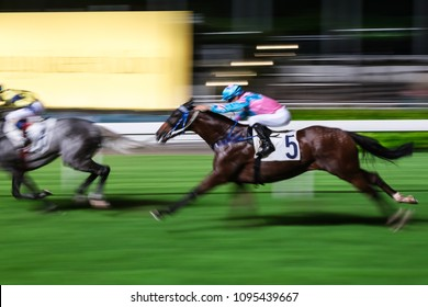 Racehorses ridden by jockeys running fast during the race at racetrack. Striving to victory. Hong Kong Happy Valley race course. Motion blur.