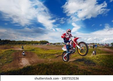 Racer jumps on trampoline motorcycles dirtbike blue sky.