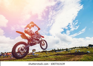 Racer jumps on trampoline motorcycles dirtbike sunset.