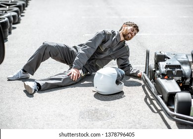 Racer lying on the track with serious injury after the accident during the race on the go-kards outdoors