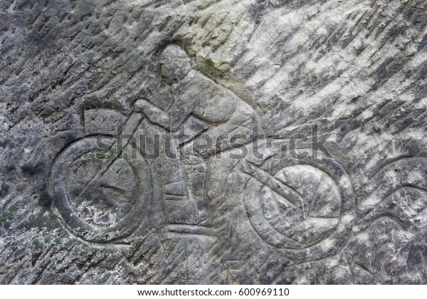 Racer on a motorbike - old rock relief, Czech republic