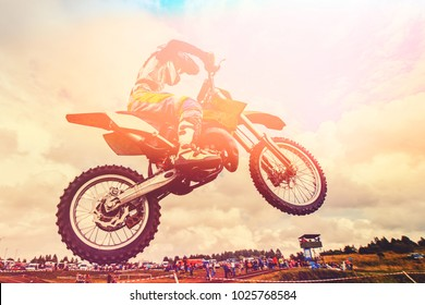 Racer on motorcycle dirtbike motocross cross-country in flight, jumps and takes off on springboard against sky. Concept active extreme rest
