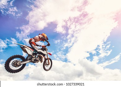 Racer on motorcycle dirtbike motocross cross-country in flight, jumps and takes off on springboard against sky. Concept active extreme rest.