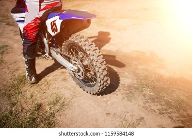 The racer on a motorcycle participates in trains on motocross in flight, jumps and takes off on a springboard against the sky. The concept of active extreme rest. The smoke and dust fly from under the