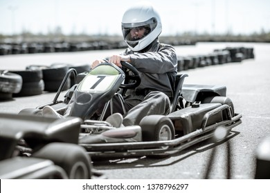 Racer in sportswear and protective helmet driving go-kart on the track