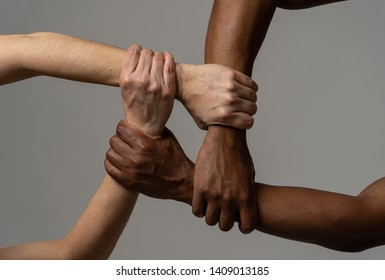 Races united against discrimination and racism. Black African American and Caucasian hands holding together in world unity and racial love and understanding. Tolerance and cooperation concept.