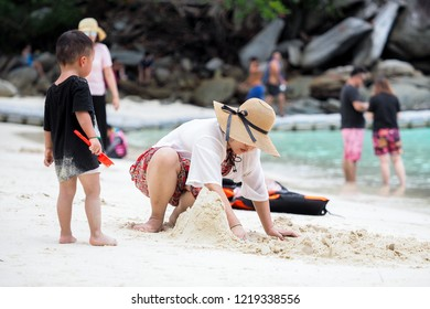 RACHA ISLAND, PUKET THAILAND- October 20, 2018 : Mother and son are intently building a sand castle on the beach with the freshy and cleary weather in the southern island  of Thailand