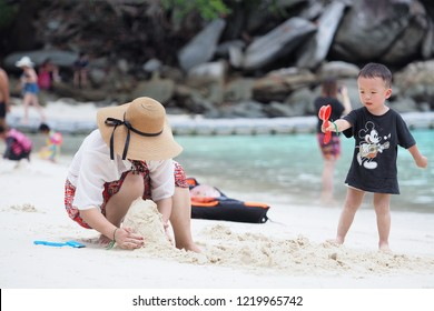 RACHA ISLAND, PUKET THAILAND- October 20, 2018 ; Mother and son are intently building a sand castle on the beach with the freshy and cleary weather in the southern island  of Thailand