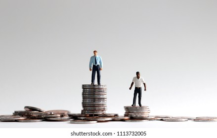 Racial wage gap concept. Miniature people standing on a pile of coins.