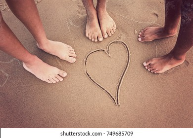 Racially diverse children's feet at the beach with a heart drawn