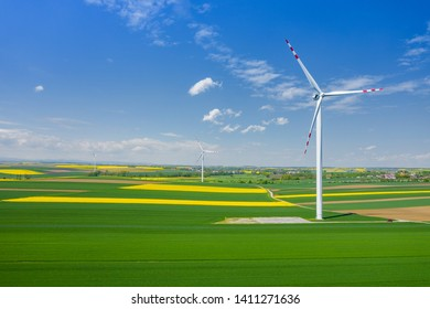 RACIBORZ, POLAND - MAY 11, 2019: Aerial view of wind turbine. Rapeseed blooming. Windmills and yellow fields from above. Agricultural fields on a summer day. Renewable Energy.