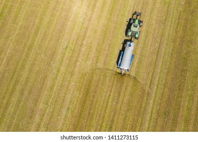 RACIBORZ, POLAND - MAY 11, 2019: Aerial view of farming tractor plowing and spraying on field.  Agriculture. View from above. Photo captured with drone.