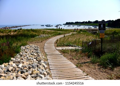 Racine, Wisconsin / USA - August 11, 2018: Walkway along the shore of Lake Michigan with many boats within the breakwater.