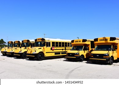 Racine, Wisconsin / USA - July 14, 2019:  A row of new school buses parked in a lot in mid summer with blue skies behind.