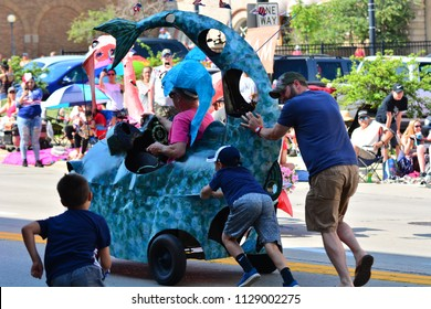 Racine, Wisconsin / USA - July 4, 2018: Racine Art Museum pedal floats racing through the parade.   Helpers running to aid the float uphill.