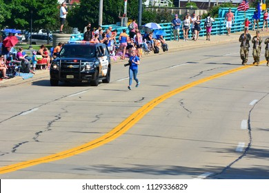 Racine, Wisconsin / USA - July 4, 2018:  A photographer running down the street to get ahead and take the shot.