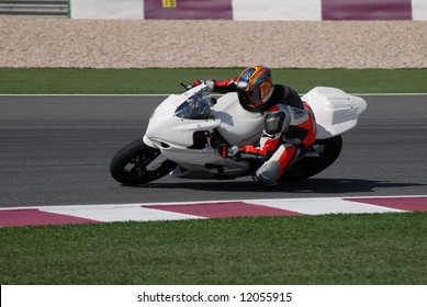 Racing bike rider leaning into a fast corner on track day.
