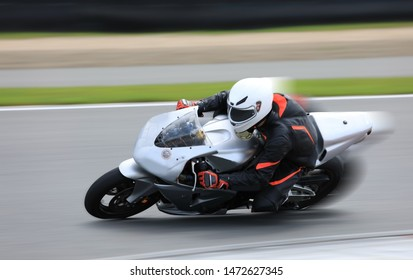 Racing bike rider leaning into a fast corner on the race track