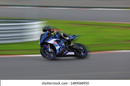 Racing bike rider leaning into a fast corner at high speed on the race track
