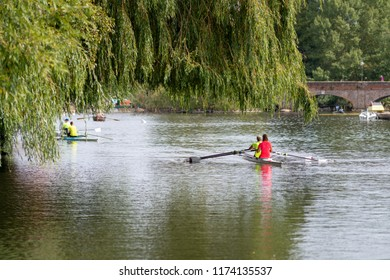 racing boats under willow tree with arched bridge in background