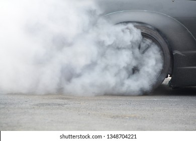 Racing Car Burning rubber Tire on Spinning wheel with white smoke on Racing Track prepare for Drift driving Competition