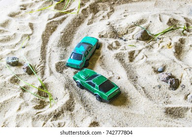 Racing cars on the sand compete in a game of survival. The machine behind the other car