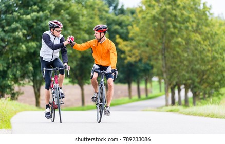 Racing cyclists after sport and fitness workout giving high five in finish
