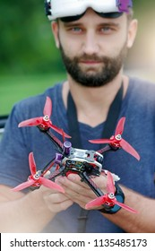 Racing drone pilot. Close-up focus on drone in the hands of pilot, blurred face of model