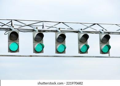 Racing green traffic light on background sky