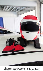 Racing helmet and glove on race car roof. Concept of  personal safety.