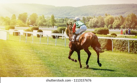 Racing horse coming first to finish line. Racehorse with jockeys during a horse race. Jockeys runs into the turn of the racetrack.